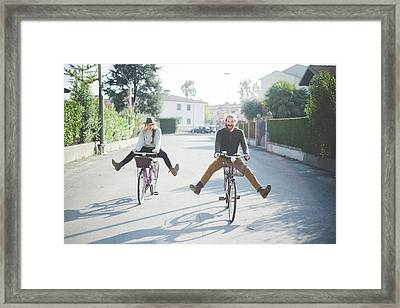 Young Couple Cycling With Legs Out Framed Print by Eugenio Marongiu