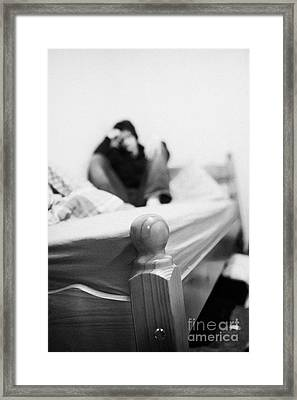 Young Dark Haired Teenage Man Sitting At The Far End Of His Bed In An Untidy Bedsit Bedroom Curled U Framed Print by Joe Fox