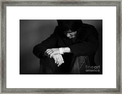 Young Dark Haired Teenage Man Sitting On The Floor With Back Against The Wall In The Fetal Position  Framed Print by Joe Fox