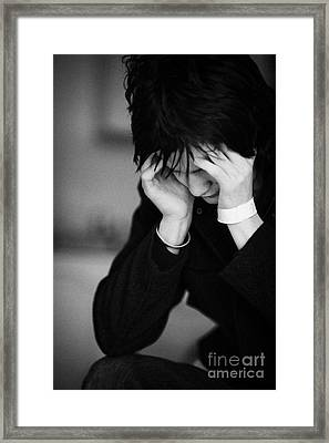 Young Dark Haired Teenage Man Sitting With His Head In His Hands Staring At The Floor Framed Print by Joe Fox