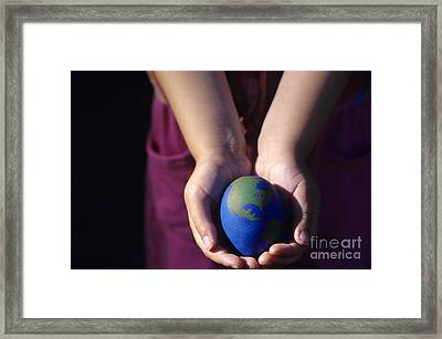 Young Girl Holding Earth Egg Framed Print by Jim Corwin
