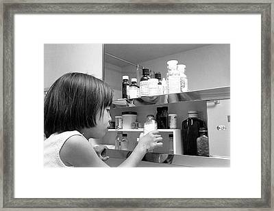 Young Girl In Medicine Cabinet Framed Print by Underwood Archives