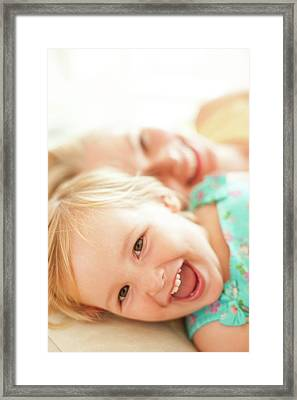 Young Girl Lying Down Laughing Framed Print by Ian Hooton
