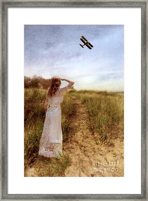 Young Lady In Vintage Clothing Watching A Biplane Framed Print by Jill Battaglia