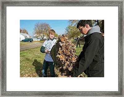 Young Volunteers Raking Leaves Framed Print by Jim West