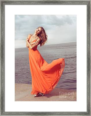 Young Woman In Orange Dress Flying In The Wind At Sea Shore Framed Print by Oleksiy Maksymenko