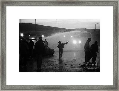 Youths Rioting Throwing Stones With Burned Out Car Being Hit By Water Canon On Crumlin Road At Ardoy Framed Print by Joe Fox