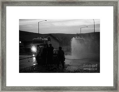 Youths Rioting With Burned Out Car Being Hit By Water Canon On Crumlin Road At Ardoyne Framed Print by Joe Fox