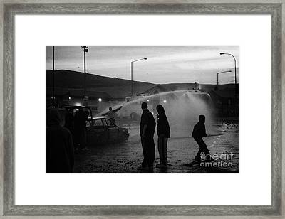 Youths Rioting With Burned Out Car Being Hit By Water Canon On Crumlin Road At Ardoyne Shops Belfast Framed Print by Joe Fox