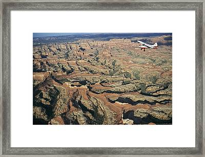 A Small Aircraft Flies Framed Print by Joel Sartore