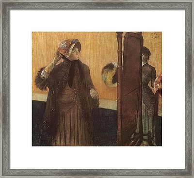 At The Milliner's Framed Print by Edgar Degas