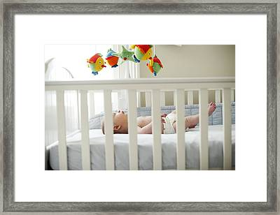 Baby Boy In His Cot Framed Print by Ian Boddy