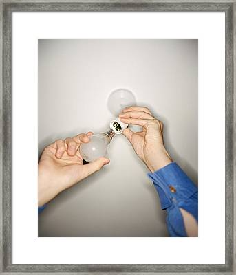 Changing Light Bulb Framed Print by Lawrence Lawry
