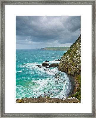 Cliffs Under Thunder Clouds And Turquoise Ocean Framed Print by Ulrich Schade