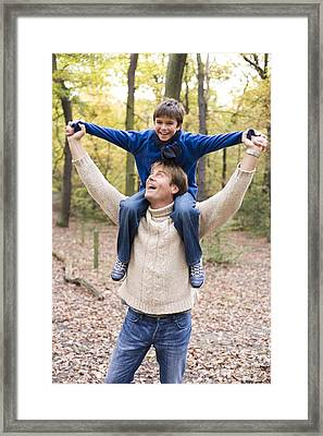 Father Carrying His Son In A Wood Framed Print by Ian Boddy