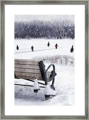 Ice Skates Hanging On Bench With People  Skating In Background Framed Print by Sandra Cunningham