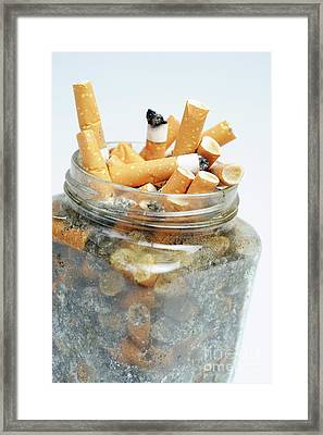 Jar Overflowing With Cigarette Butts Framed Print by Sami Sarkis