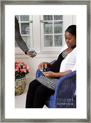 Pregnant Woman Taking Vitamins Framed Print by Photo Researchers