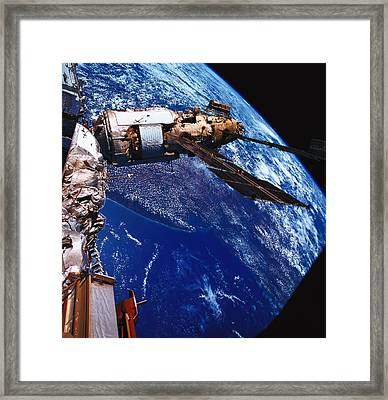 A Satellite Orbiting Above The Earth Framed Print