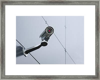 A Security Camera Mounted On The Wall Framed Print by Jaak Nilson