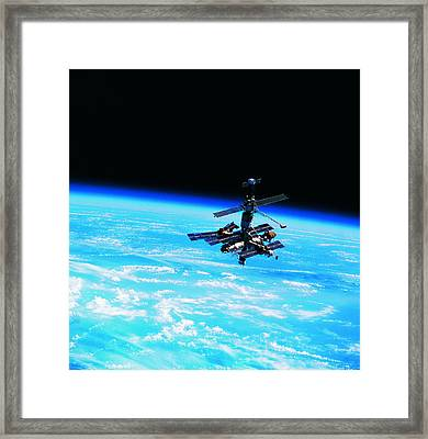 A Space Station Orbiting Above Earth Framed Print by Stockbyte