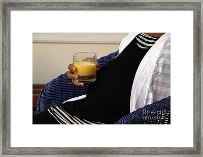 Pregnant Woman Drinking Orange Juice Framed Print by Photo Researchers