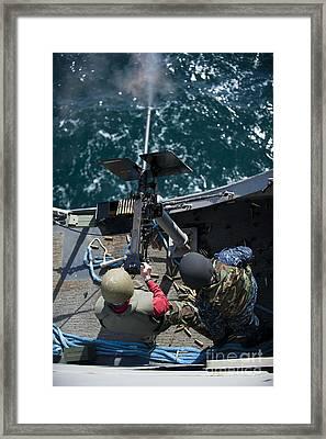A Sailor Fires A .50-caliber Machine Framed Print by Stocktrek Images