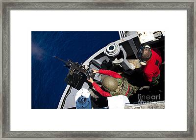 A Sailor Fires A .50-caliber Machine Framed Print by Stocktrek Images