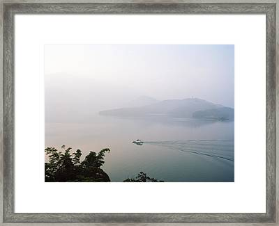 A Boat Cuts Into The Still Waters Framed Print by Justin Guariglia