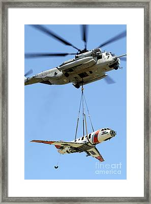 A Ch-53 Sea Stallion Lifts A Hu-25 Framed Print by Stocktrek Images