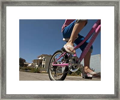 A Child Rides Her Bike Along The Beach Framed Print by Stacy Gold