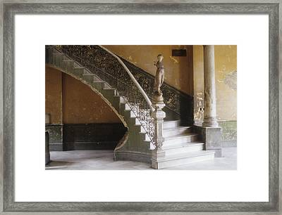A Circular Marble Staircase And Statue Framed Print by Kenneth Ginn
