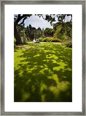 A Couple Sits On A Dappled Lawn Framed Print by Taylor S. Kennedy