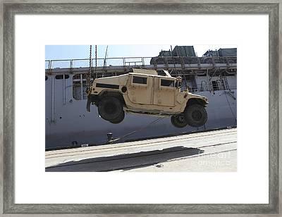 A Crane Lifts An M998 Humvee Framed Print