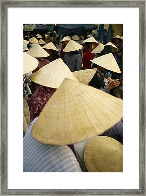 A Crowd Of People In Conical Straw Hats Framed Print by Justin Guariglia