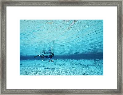 A Diver Swims Through Crystal Rivers Framed Print by Raul Touzon