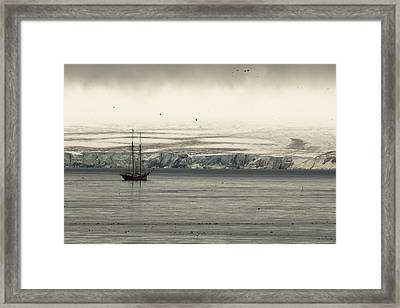 A Double-masted Sailboat Floats Near An Framed Print by Norbert Rosing