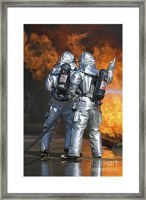 A Firefighter Fights A Fire Framed Print