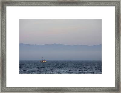 A Fishing Boat Sails Along At Sunset Framed Print by Taylor S. Kennedy