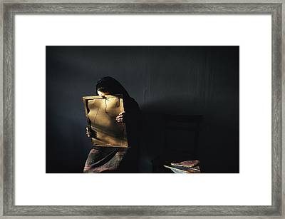 A Grieving Woman Holds A Photograph Framed Print by James L Stanfield