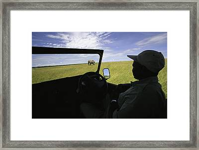 A Guide In A Jeep Observing An African Framed Print by Michael Melford