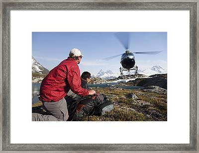 A Helicopter Picks Up Two Men Framed Print