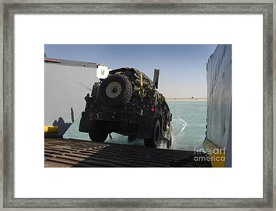 A Humvee Drives Down The Ramp Framed Print by Stocktrek Images
