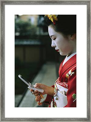 A Kimono-clad Geisha Dials Her Cell Framed Print by Justin Guariglia
