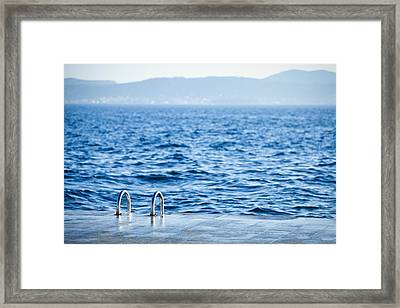 A Ladder Leading Down To The Water Framed Print