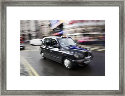 A London Cab Traveling Through Traffic Framed Print by Justin Guariglia