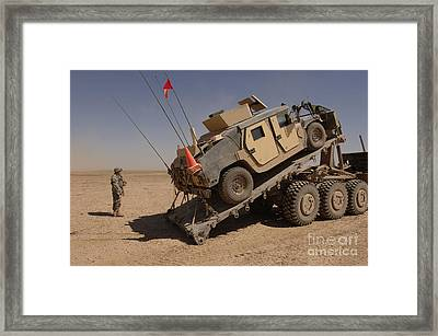 A M1114 Armored Vehicle Is Unloaded Framed Print by Stocktrek Images