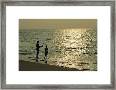 A Man And A Young Boy Fish In The Surf Framed Print by Medford Taylor