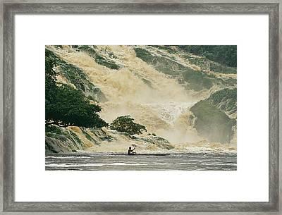 A Man On A Canoe Near The Crashing Framed Print
