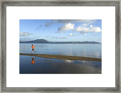 A Man Running On A Beach Is Reflected Framed Print by Bill Hatcher